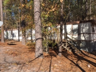 3 bedroom 2 bath mobile home sitting on wooded lot Kitchen with large pantry New flooring through