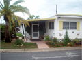 2 bdrm 1 bath mobile home with porch lanai carport roof over plants bushes shed has character