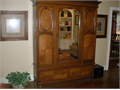 Antique solid oak turn-of-the-century English armoire with original hardware  Has beveled mirror