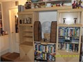 Light brown or tan wood entertainment center with added shelves as TV stand Lots of storage space